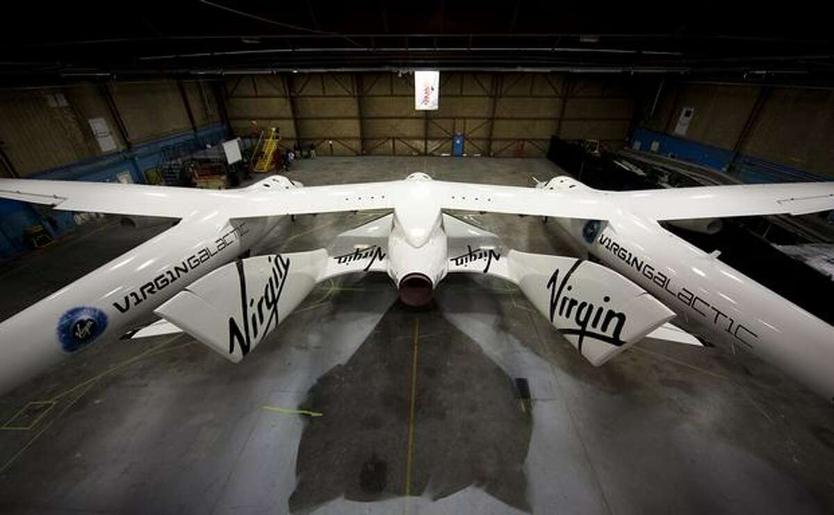Virgin Galactic's SpaceShipTwo beneath White Knight Two, which will ferry SpaceShipTwo to launch altitude, on Dec. 7, 2009 at the Mojave Air and Space Port in Mojave, Calif. (Virgin Galactic photo)