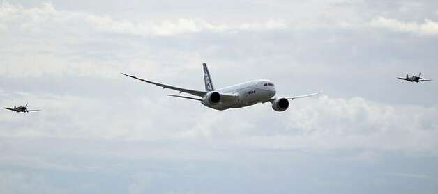 Boeing's third 787 Dreamliner, ZA003, is accompanied by two Spitfire airplanes during a flypast at the 2010 Farnborough International Airshow, in Farnborough, England. Photo: Getty Images
