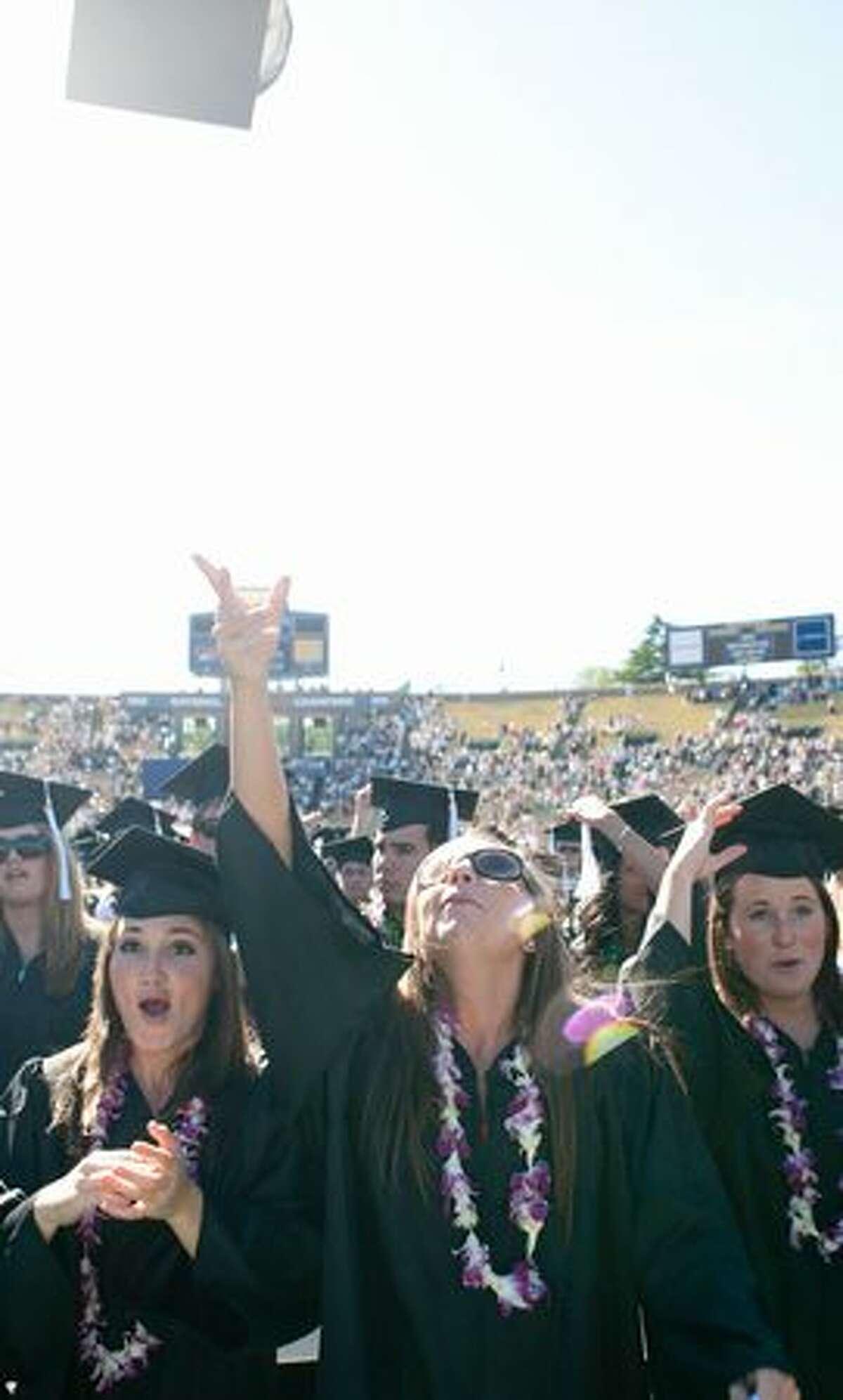 Graduates throw their caps as the ceremony concludes.
