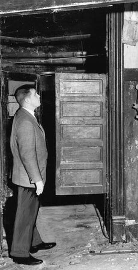 Bob Ashley, chairman of the Seattle Junior Chamber's Community Development Committee in January 1964, stands by swinging doors of old saloon that was destroyed by the Great Seattle Fire, according to a P-I story at the time. The saloon, which was also believed to be an opium den, was below Third Avenue South and South Washington Street. Photo: P-I File