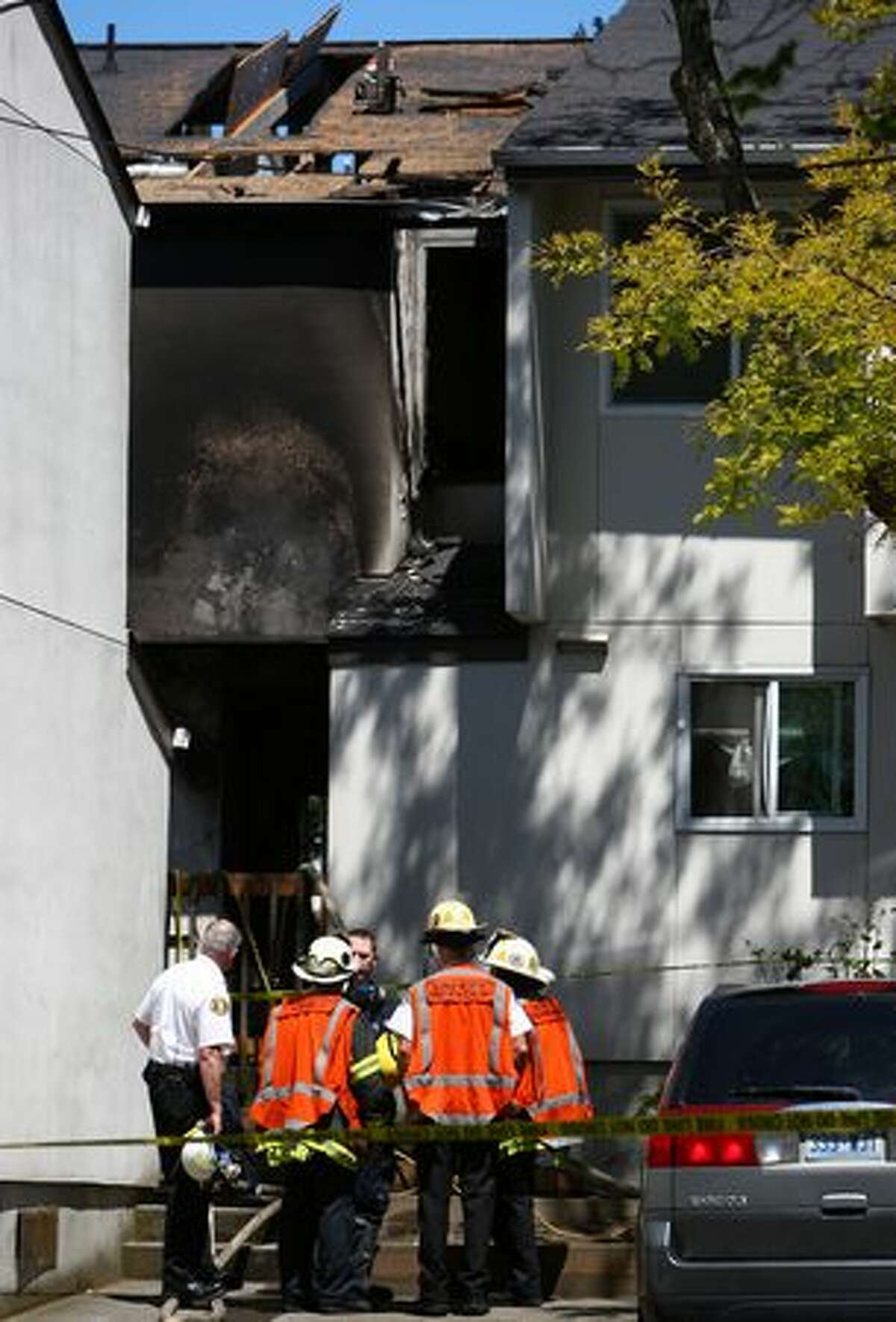Firefighters and investigators look over the scene after a fire in an apartment building killed five people in Seattle's Fremont neighborhood. Some neighbors complained about the response to the fire after a truck broke down and firefighters experienced technical difficulties extinguishing the fire.