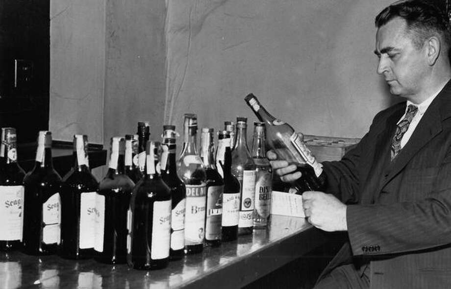 "Sgt. Loren Meece admires a bottle of liquor during the ""Gold Braids"" raids at Cabbie's Club, Nov. 30, 1947. Photo: P-I File"