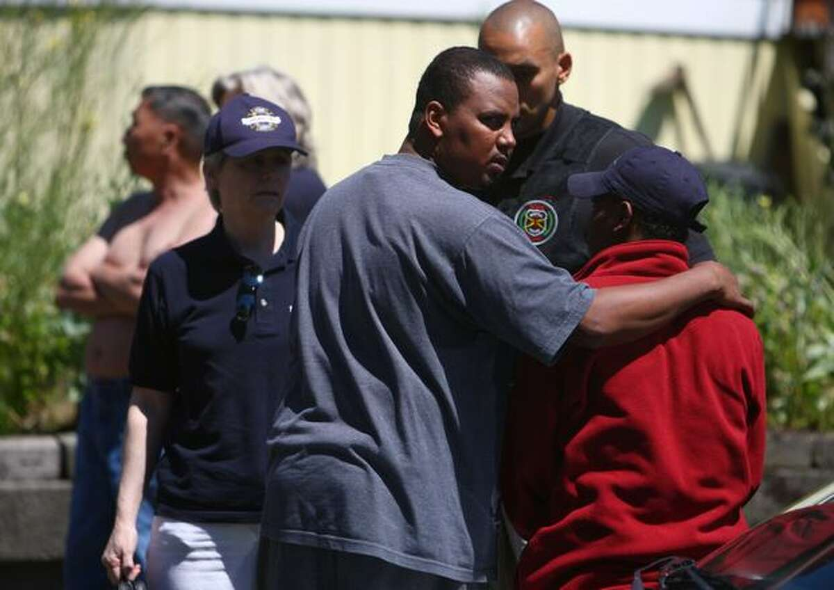 A man is comforted after a fire in an apartment building killed five people in Fremont. It was reported that children were among the dead in the fire.