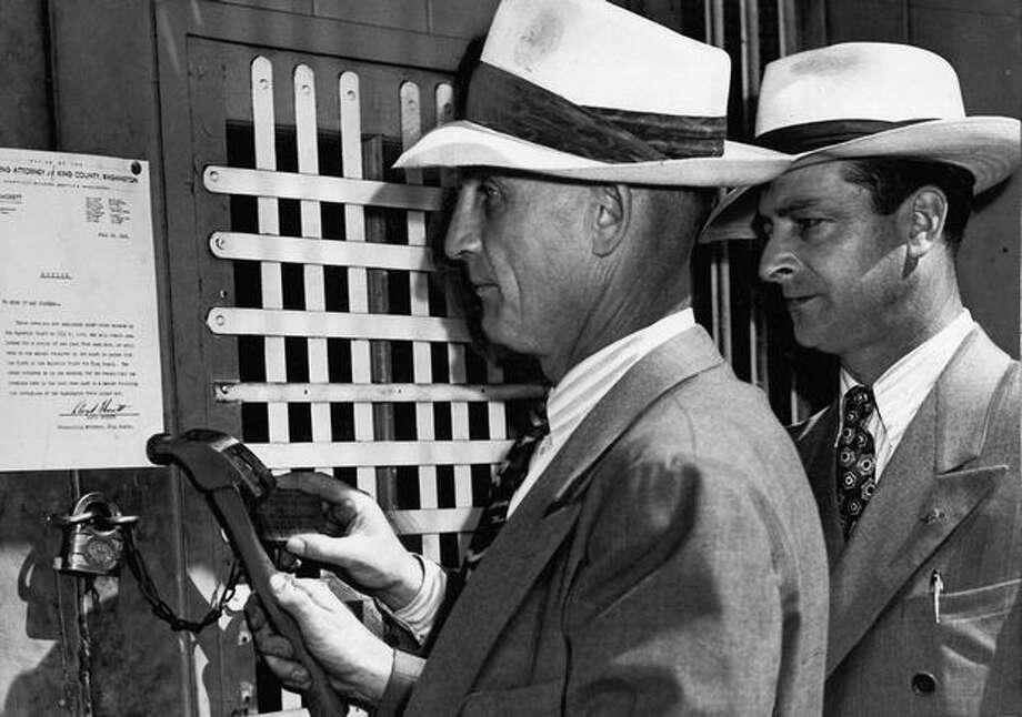 Sheriff Harlan S. Callahan, left, and Richard K. Engle, of the King County Prosecutor's Office, posted an abatement notice at a nightclub, 420 Second Ave. S. The picture was taken in July 1945. Photo: P-I File