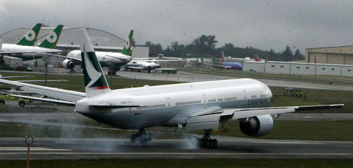 A Cathay Pacific Boeing 777 lands at Paine Field, in Everett.