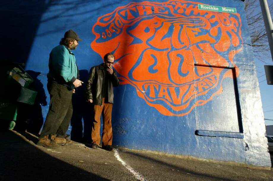 Brandon Wald, left, and Christian Reise contemplate the white chalk line drawn around the Blue Moon tavern on Dec. 8, 2005. That day, a new law required smokers to be at least 25 feet from the door. (Joshua Trujillo photo) Photo: P-I File