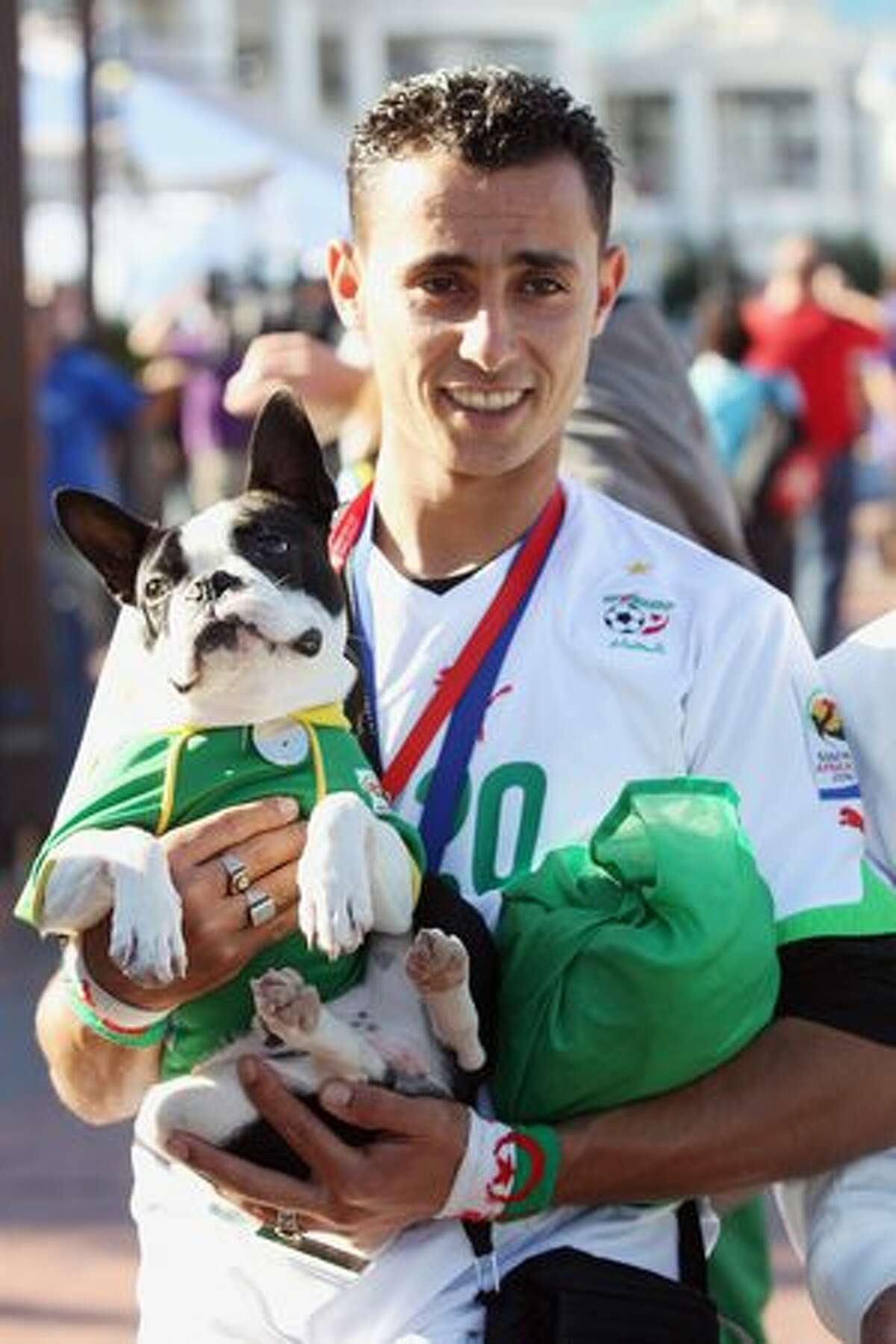 An Algerian fan stands with his dog on the waterfront in Cape Town, South Africa. Cape Town hosts the match between England and Algeria in the second of their group stage matches on Friday.
