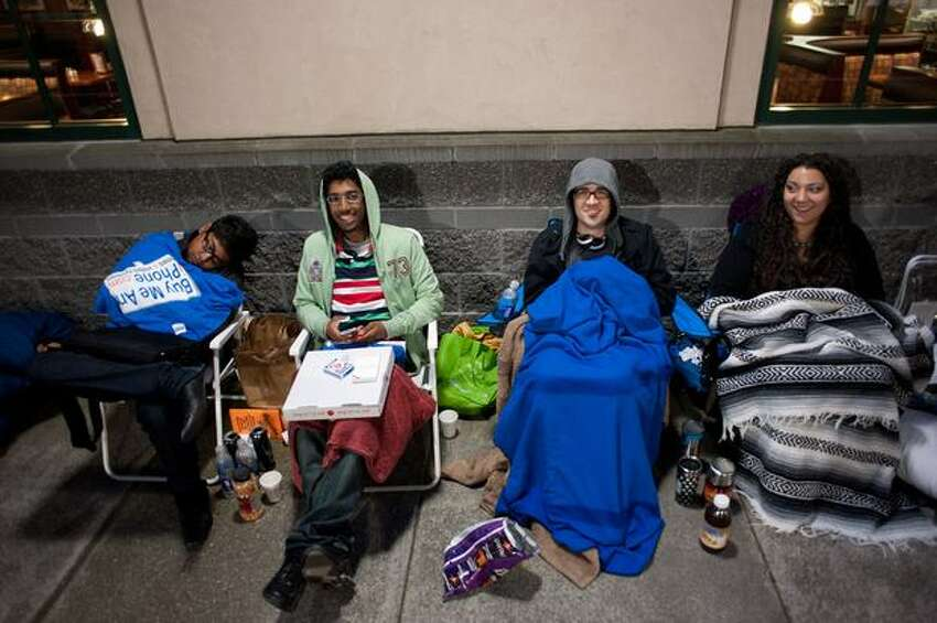 From left to right: Flo Wsion, Matt Saba, Jay Wade and Tanya Hemion wait in line for the new iPhone at the Apple store at University Village in Seattle. They started waiting at 10 p.m. on Wednesday.