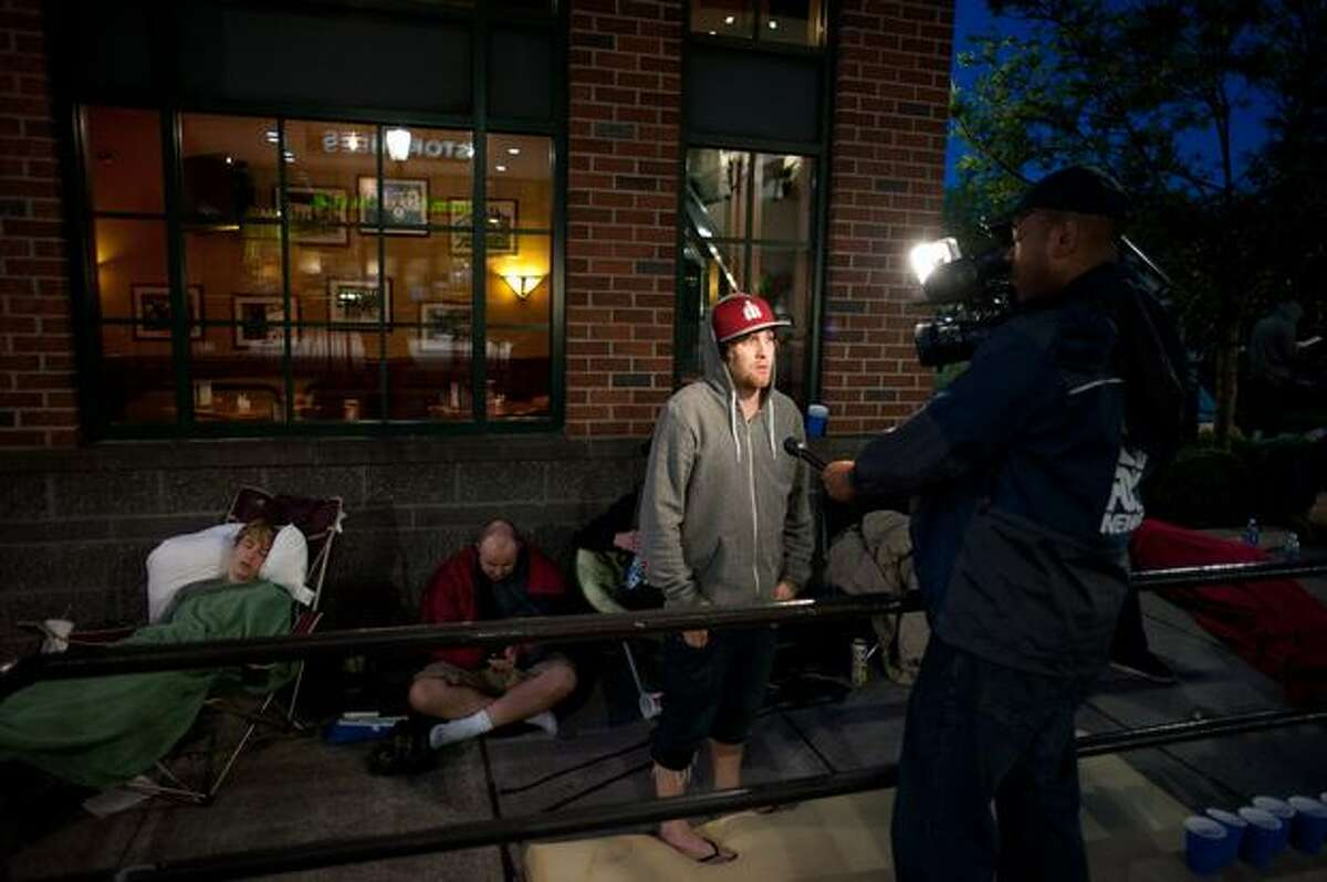 A person from the wait line is interviewed by a cameraman as he waits in line for the new iPhone at University Village in Seattle.