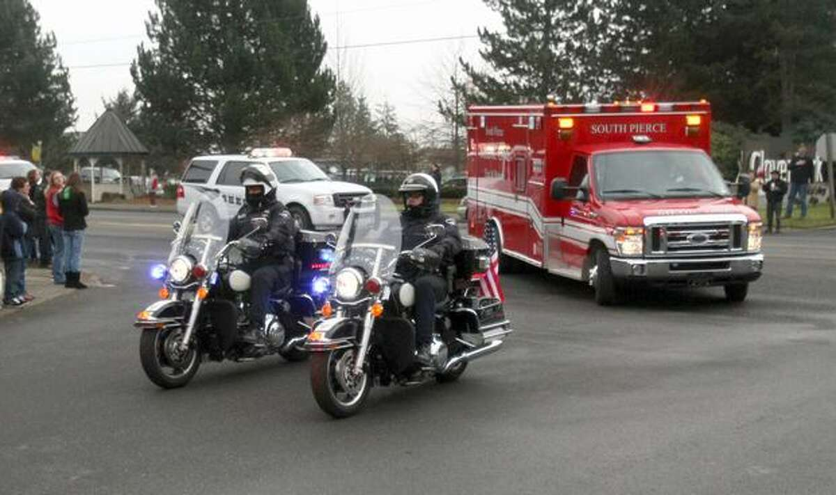A motorcade transporting the body of Mundell arrives at the Mountain View Funeral Home.
