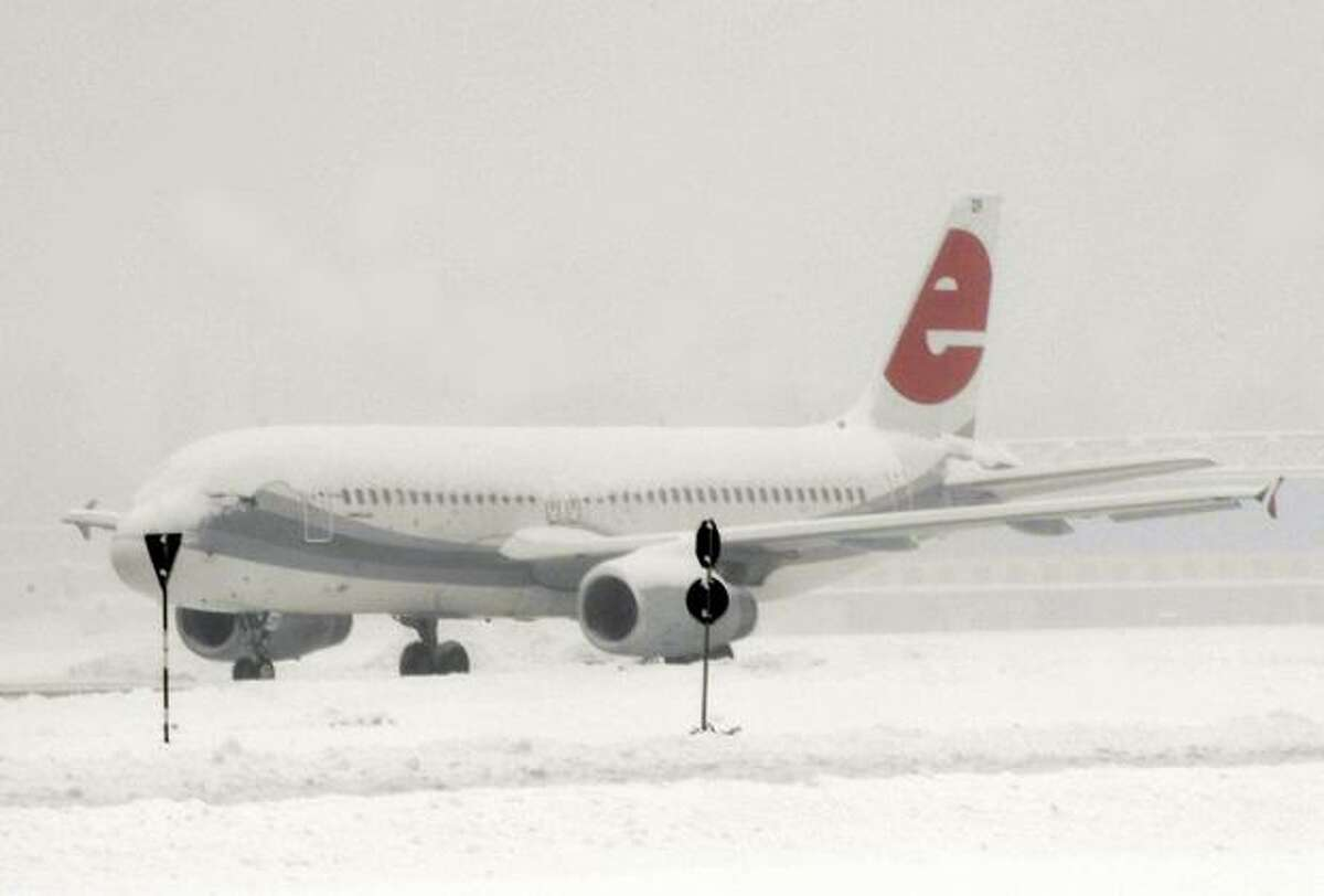 An aircraft covered in snow stands on the tarmac at Milan's Linate airport, on Dec. 22, 2009. All flights were canceled at Milan Malpensa airport, which was expected to stay closed until midday (1200 GMT), the airline added.