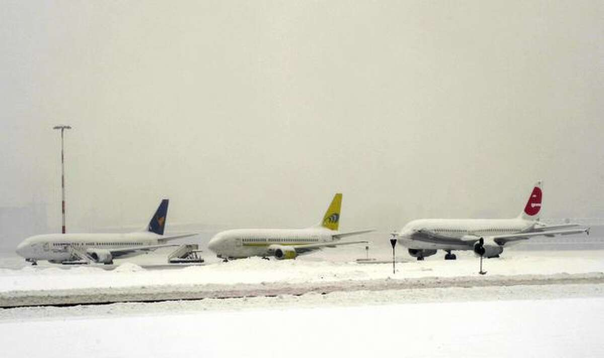Aircraft covered in snow stand on the tarmac at Milan's Linate airport, on Dec. 22, 2009. All flights were canceled at Milan Malpensa airport, which was expected to stay closed until midday (1200 GMT), the airline added.