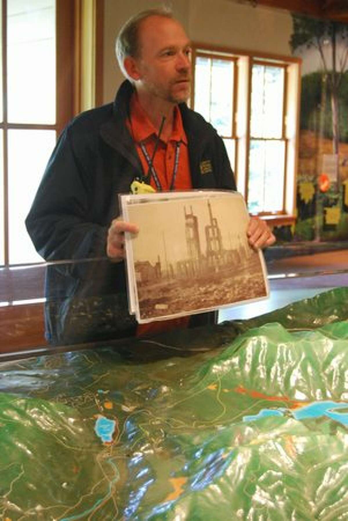 Ralph Naess, public education specialist for Seattle Public Utilities, holds up a picture of the Great Seattle Fire in front of a model of the Cedar River Watershed.