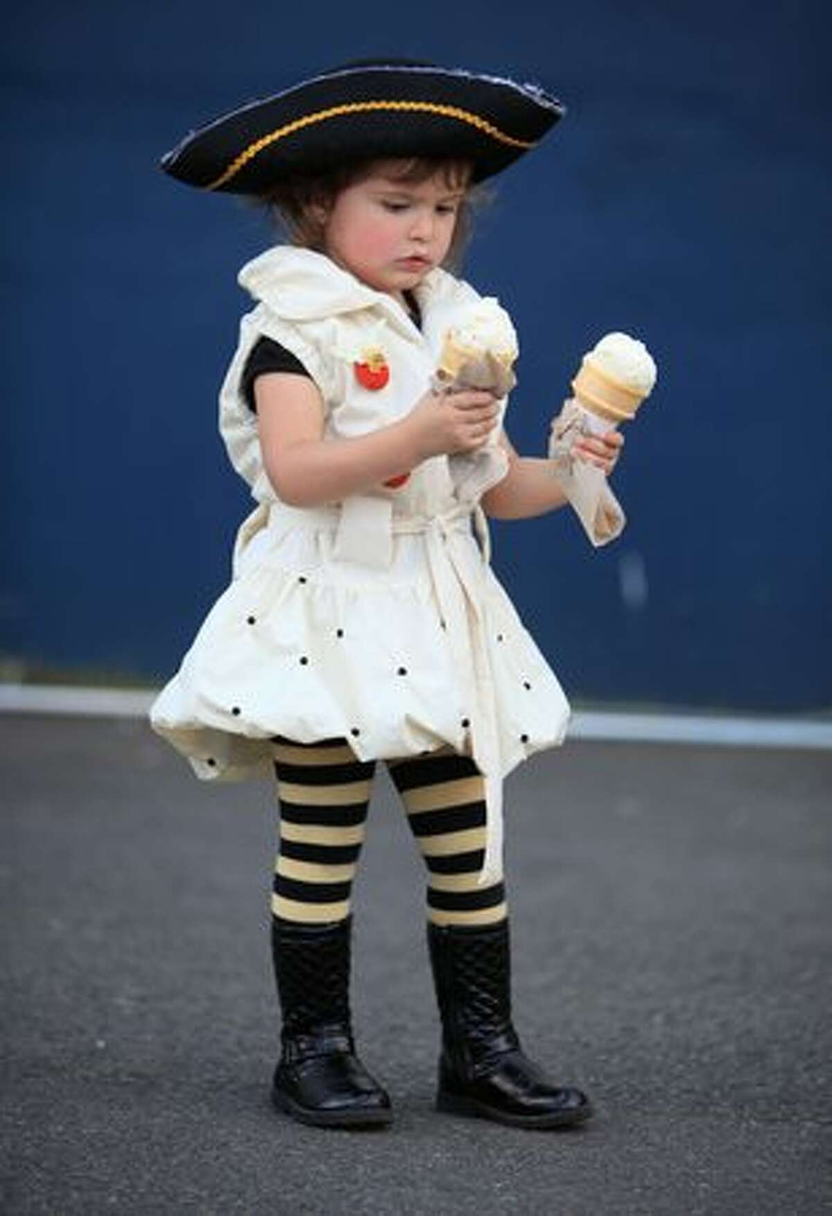 Layla Noel, 2, holds onto a pair of ice cream cones during the Lake Union Wooden Boat Festival.