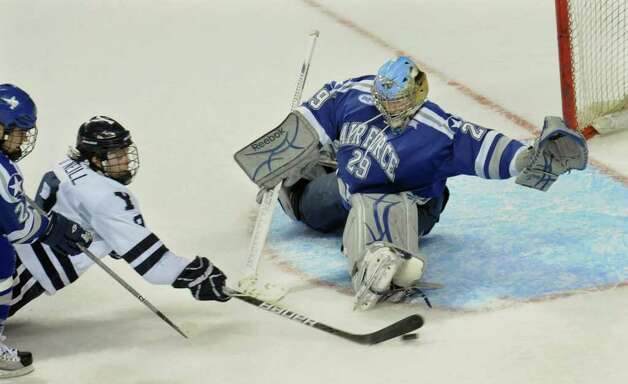 Yale's #9 Brian O'Neill dives towards the puck in a goal attempt against Air Force, during NCAA hockey tournament action at the Webster Bank Arena at Harbor Yard in Bridgeport on Wednesday March 25, 2011. Guarding the net is goalie Jacob Musselman. Photo: Christian Abraham / Connecticut Post