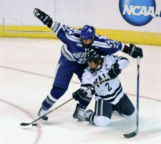 While down on the ice, Yale's #2 Jimmy Martin tries to get the puck away from Air Force's #27 John Kruse, during NCAA hockey tournament action at the Webster Bank Arena at Harbor Yard in Bridgeport on Wednesday March 25, 2011. Guarding the net is goalie Jacob Musselman. Photo: Christian Abraham / Connecticut Post