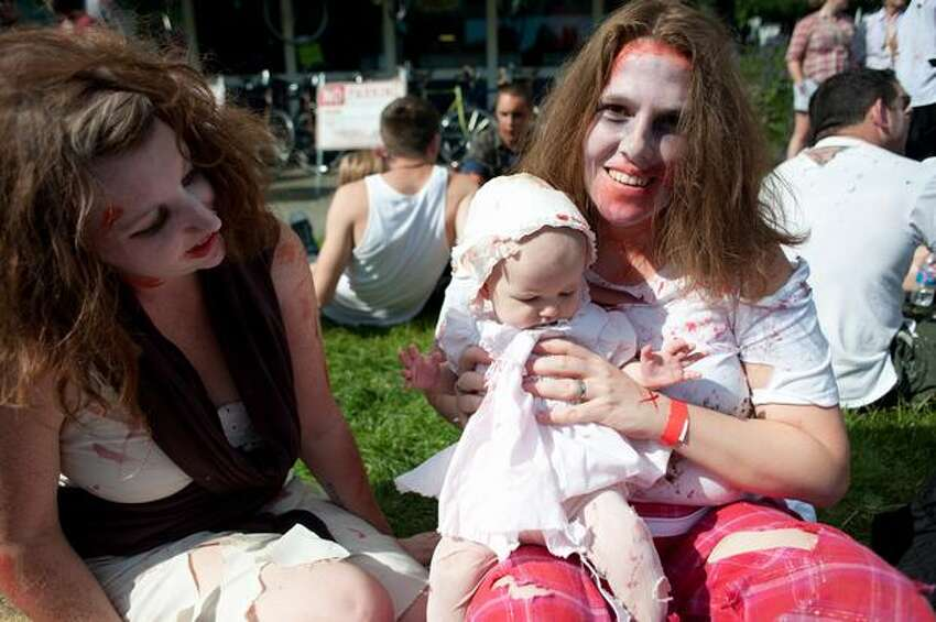 Alise Robertson, and Amanda Clifford hold 5 month old Talulla McAlister during the annual Zombie Walk in Fremont.