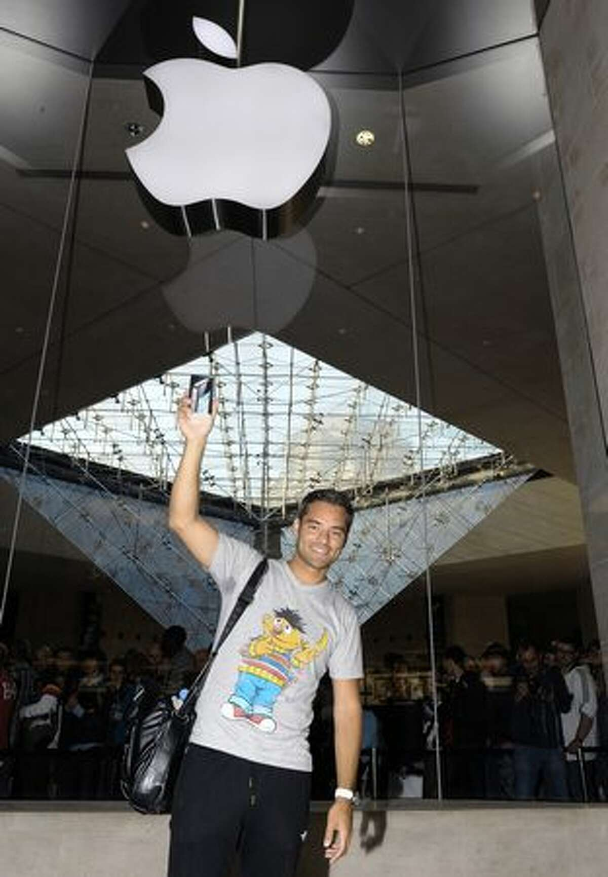 Maurice holds his new iPhone 4 in front of a mobile-phone store at the Carrousel du Louvre shopping mall in Paris on June 24, 2010.
