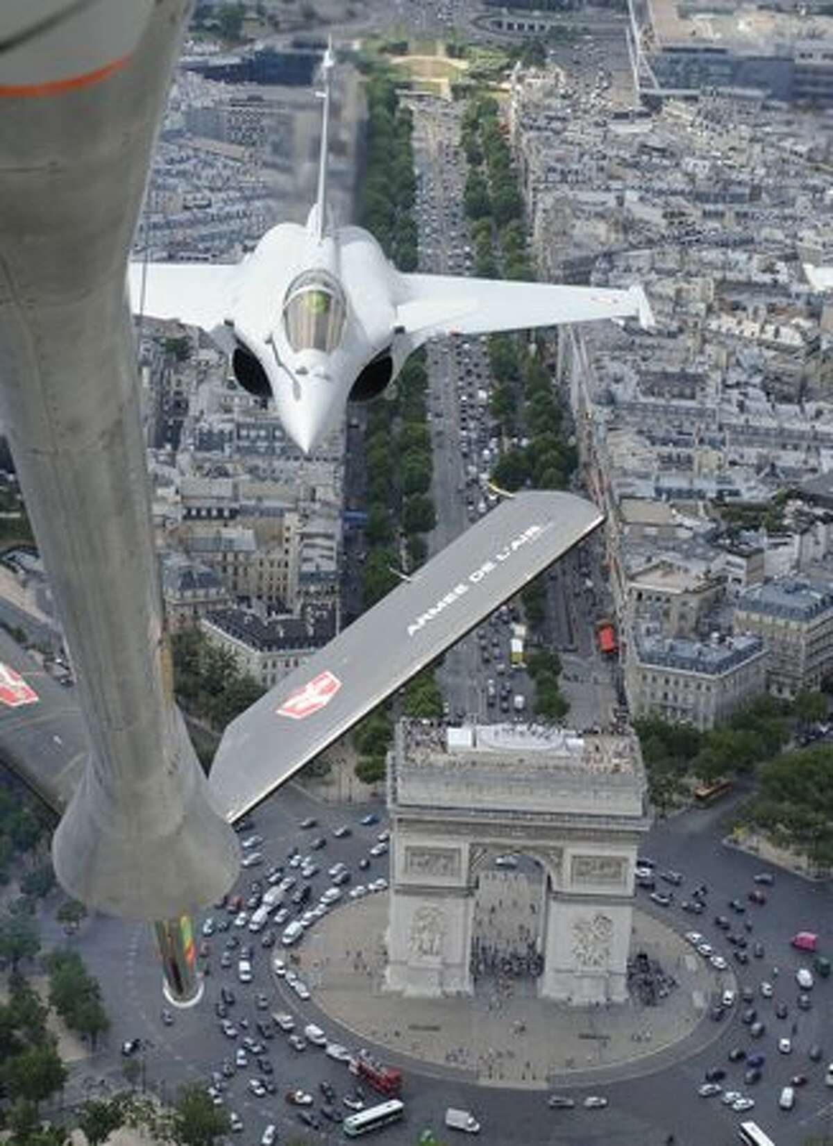 A photo taken from a French refueling tanker shows French Rafale jet fighters during a training session above the Arc of Triumph in Paris prior the July 14 Bastille Day military parade.