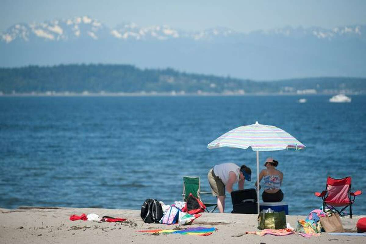A family sets up an umbrella and lays out towels at Alki Beach on a day when temperatures broke the 90-degree mark.