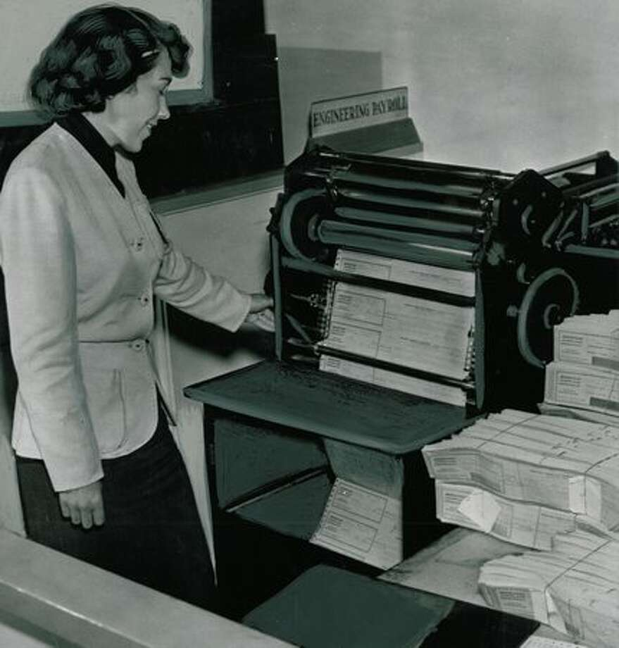 At this machine, operated by payroll clerk Dores Robinson, 18,500 hourly payroll checks receive the signatures of Boeing president William M. Allen and treasurer Harold E. Bowman. The photo was taken in 1951. Photo: P-I File