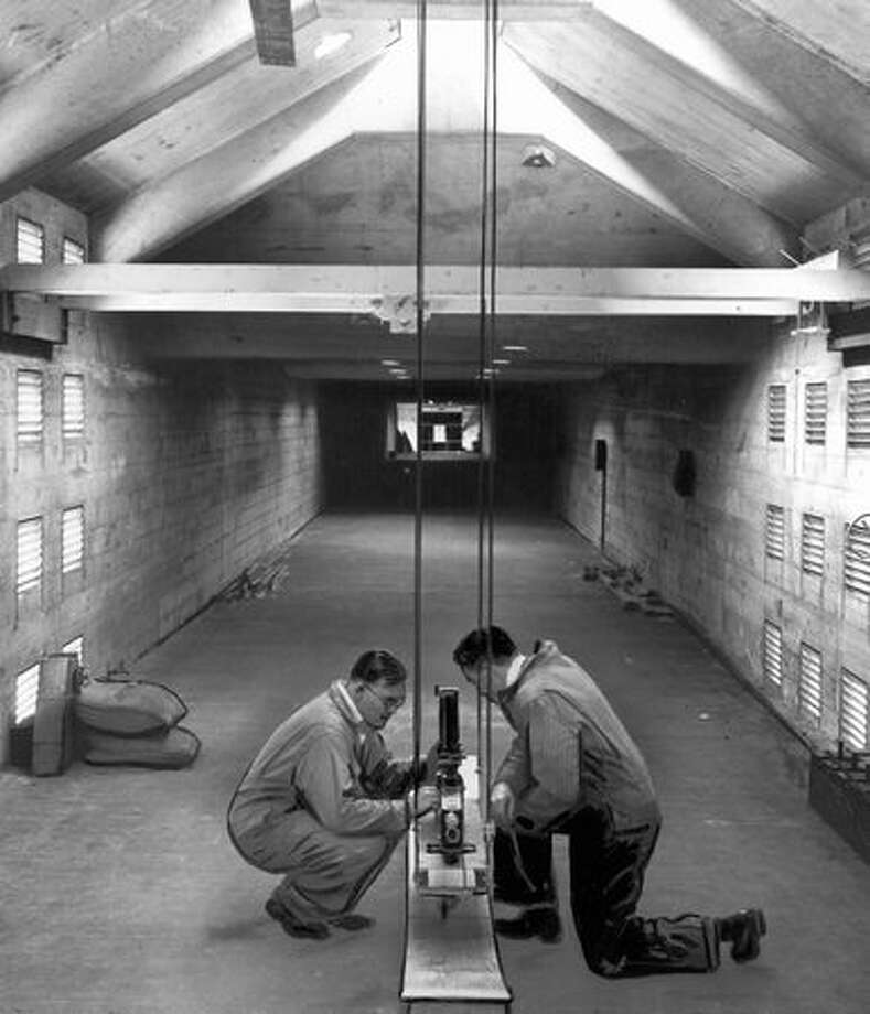 The ballistics pendulum being adjusted here in 1944 by Don Free and Rachard Falconer measured the kick of a machine gun. Photo: P-I File