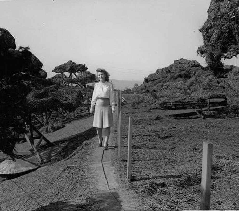 The 1945 caption for this photo states: Miss Offenbach strolls through the Boeing camouflage country over the mile and one-half long catwalk designed for fire protection and anti-aircraft purposes. Photo: P-I File