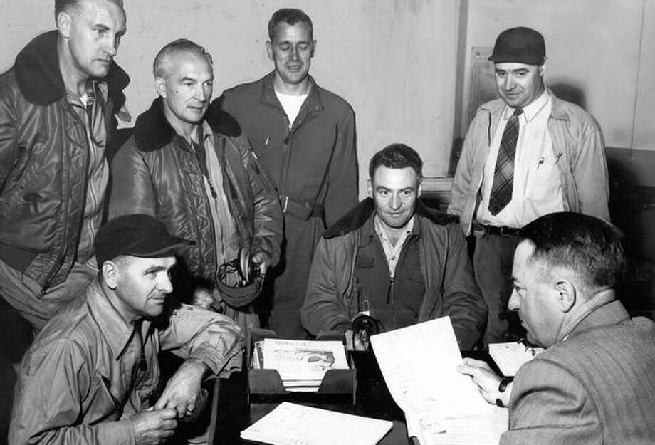 Briefing Boeing production test flight crew, left to right, G. V. Smith, pilot; Ben Zylstra, radar; Frank Minert, flight technician; Fred Tunnell, co-pilot, Don Kelly, flight engineer, and, back to camera, Clayton Scott, chief of production flight in 1951. Photo: P-I File