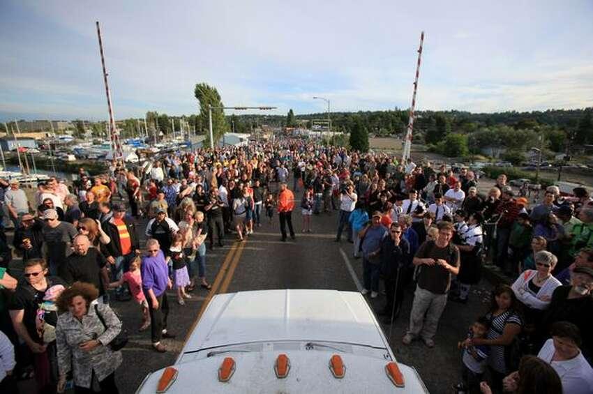 The last car crosses the South Park Bridge, through a sea of people.