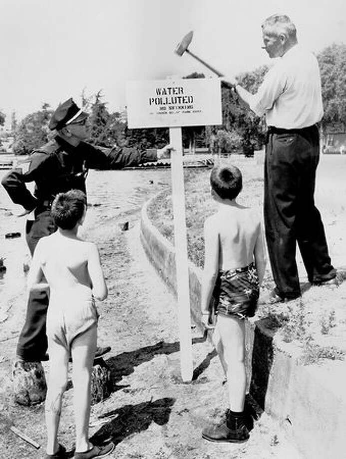 Seattle Police Sgt. Frank Patterson watches Gordon Newell post a sign about polluted water at Green Lake, June 19, 1958. Mike Smith, 9, and Charles Henderson watch. (Phil Webber/Seattlepi.com file) Photo: P-I File