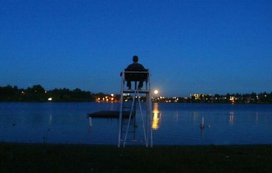 The August 2004 caption read: Richard Clairmont meditates while sitting on a lifeguard's chair at Green Lake as a full moon raises above the skyline. (Grant M. Haller/Seattlepi.com file) Photo: P-I File