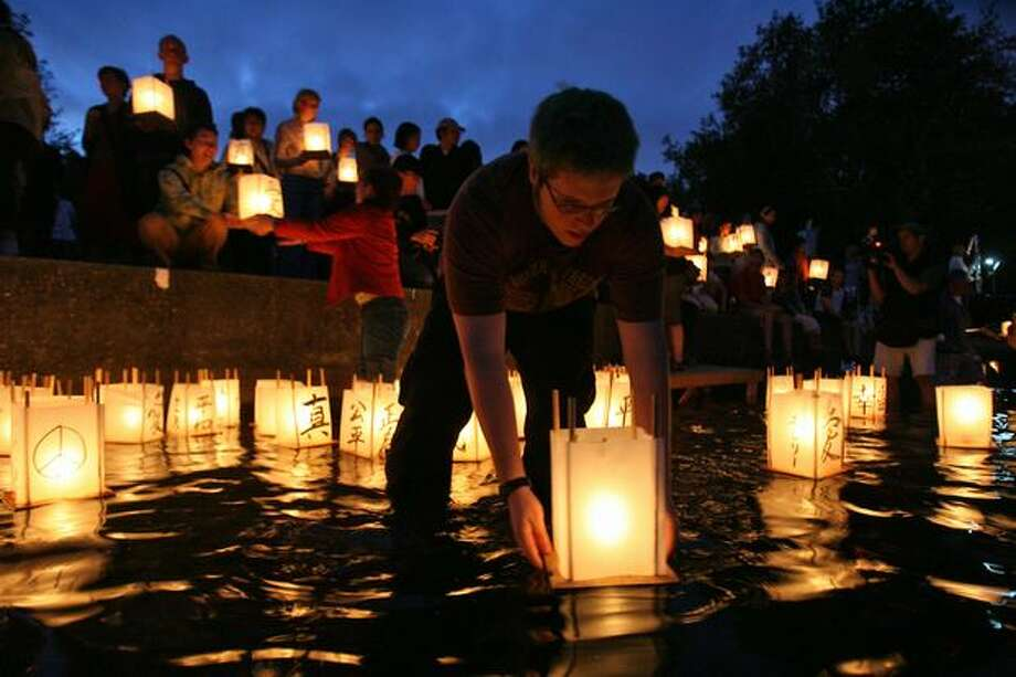 Volunteer Greg Wright of Seattle shepherds lanterns to deeper water during the Hiroshima to Hope event held at Green Lake, Aug. 5, 2007. (Mike Urban/Seattlepi.com file) Photo: P-I File