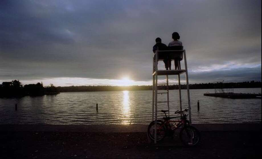 A mother and her son watch the last rays of sun disappear in the west from one of the best vantage points on Green Lake, Oct. 23, 1995. (Jeff Larsen/Seattlepi.com file) Photo: P-I File