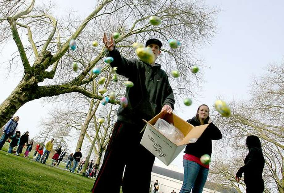 In this 2008 photo, Thomas Bohan scatters chocolate eggs for the kids prior to the start of the March 22 egg hunt at the Green Lake Community Center. (Scott Eklund/Seattlepi.com file) Photo: P-I File