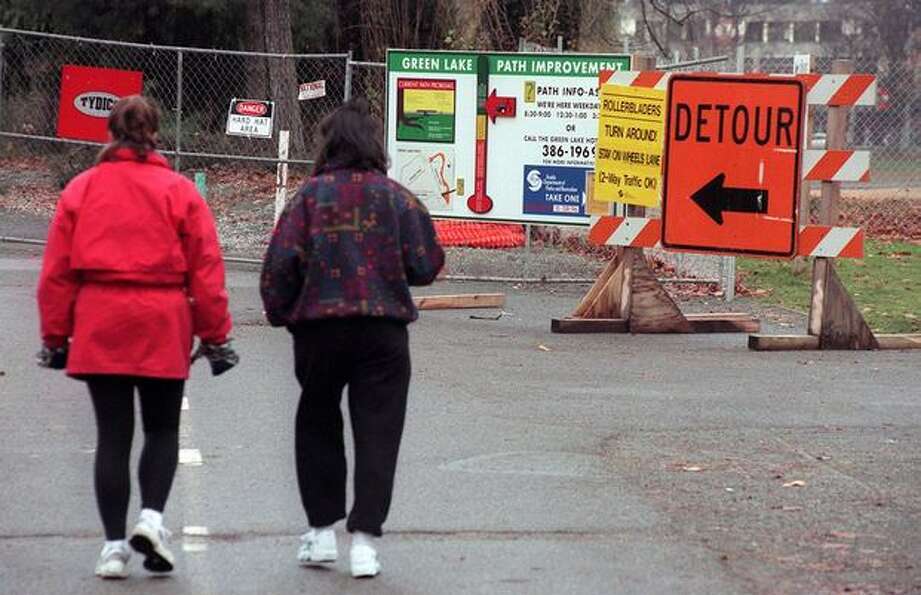 Morning walkers are detoured around the north side of the Greenlake pedestrian path which was closed