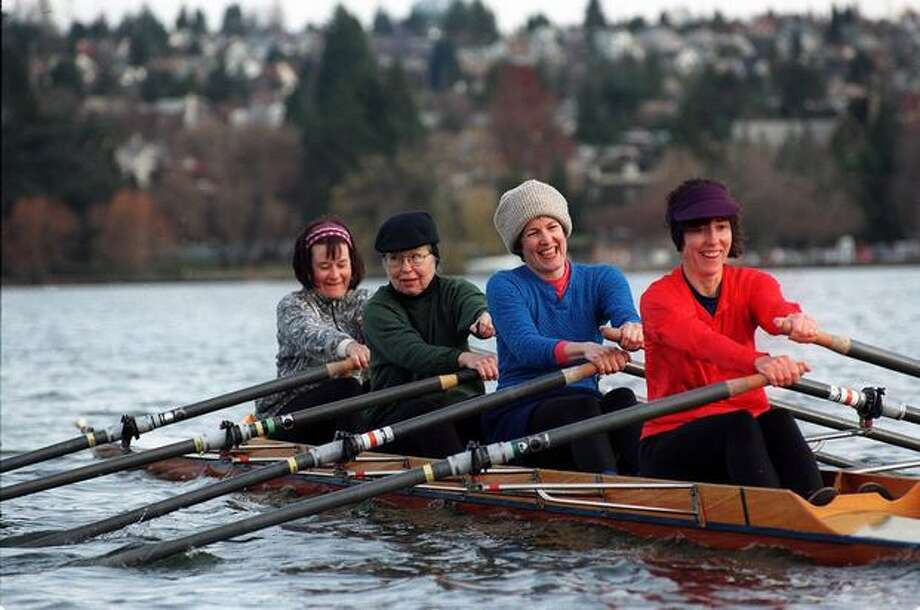 The December 1996 caption read: Despite the icy morning chill, these four members of an intermediate sculling class at Green Lake's Small Craft Center enjoy their time on the water. Photo: P-I File