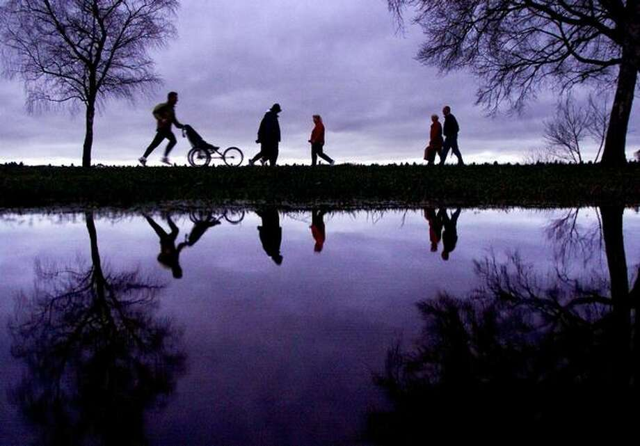 People are reflected in a large puddle at Green Lake near dusk, Jan. 8, 2002. (Dan DeLong/Seattlepi.com file) Photo: P-I File