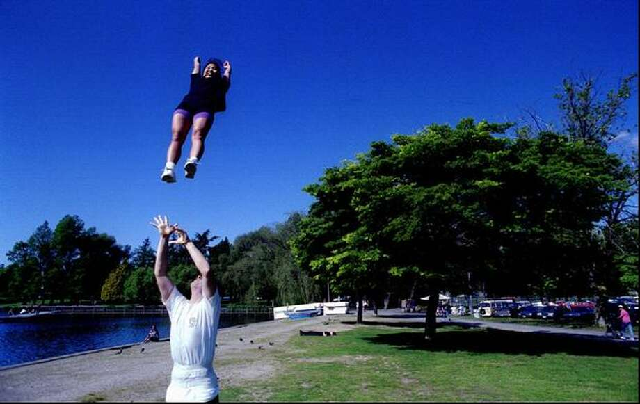 The May 1995 caption read: University of Washington cheerleader Aaron Rimmer tosses fellow cheerleader Marci Nakanishi up at Green lake while the two practiced some of their routines. They were joined by six other cheerleaders as the squad took advantage of the beautiful spring day. (Scott Eklund/Seattlepi.com file) Photo: P-I File
