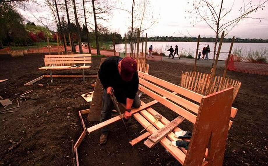The April 1997 caption read: Seattle Parks Department's Ari Heiskanen works on a pair of new benches facing the wading pool on the north end of Greenlake as walkers and joggers try out the recently repaired path which is partially completed. The wading pool should be done by the first week in May and the rest of the renovation by early summer according to Heiskanen. Photo: P-I File