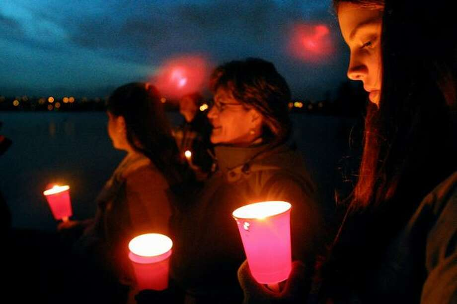 Megan Coggeshall, right, Heidi Anderson, center, and Caitlin Coggeshall, left, joined about 300 hundred people in prayer on the banks of Greenlake Dec. 31, 2002. It was the fourth annual New Year's Eve Walking Meditation for Compassion and Peace. Photo: P-I File