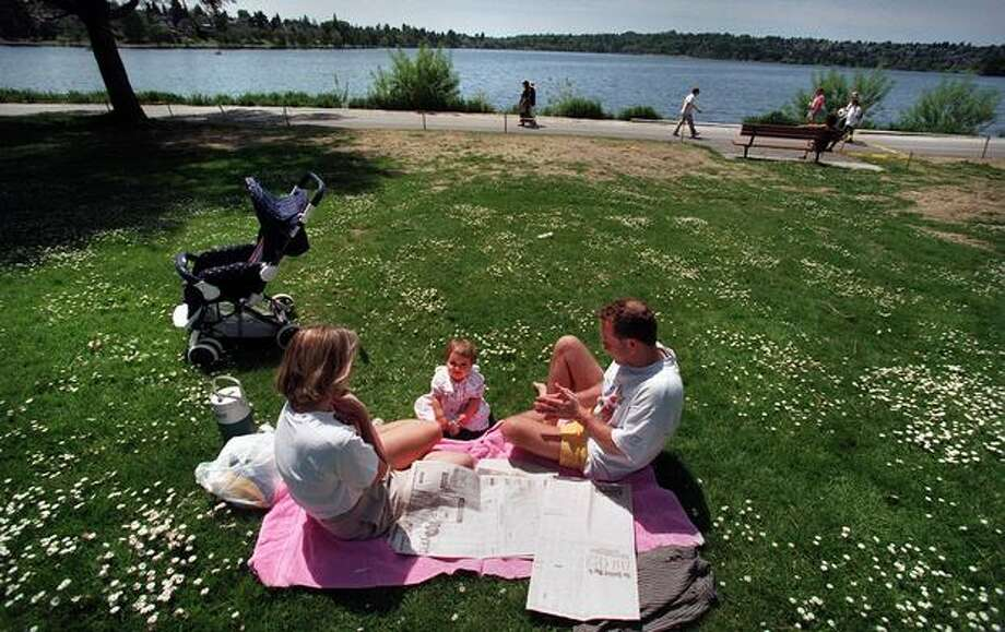 The May 1997 caption read: Enjoying the summer like weather, Cheryl Leivestad and her husband Greger had a picnic Tuesday afternoon with their 16 month daughter Anna on the north bank of Green Lake. Photo: P-I File