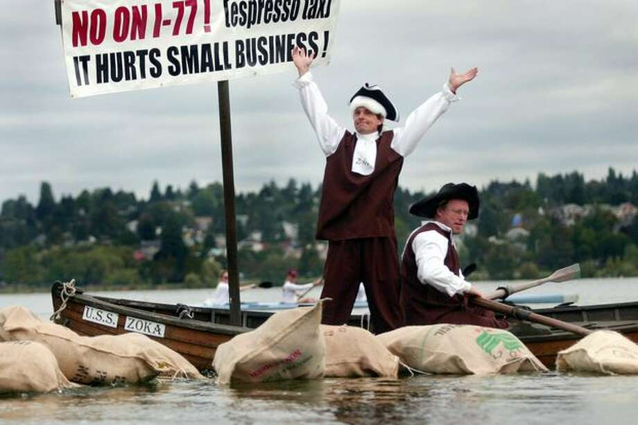 The Sept. 2003 caption read: Jeff Babcock, proprietor of Zoka Coffee Roaster and Tea Company, raises his arms after throwing burlap sacks fulled with balloons - representing coffee - into Greenlake as a protest against the proposed tax on espressos in Seattle. The demonstration mimicked the tactics used during the Boston Tea Party as early Americans protested a British tax on tea. (Joshua Trujillo/Seattlepi.com file) Photo: P-I File