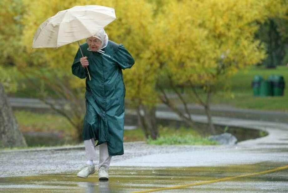 Elizabeth George battled wind and rain during her regular walk around the north end of Greenlake on Oct. 15, 2003. (Joshua Trujillo/Seattlepi.com file) Photo: P-I File