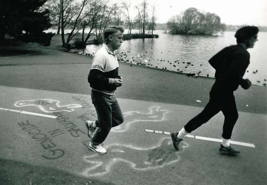 The painted outlines of about 20 bodies as well as slogans protesting El Salvador death squads showed up on the paths around Green Lake in April 1990. (Phil H. Webber/Seattlepi.com file) Photo: P-I File