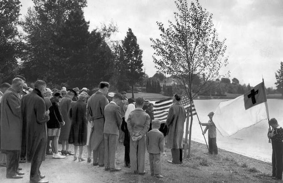 Standing with bowed heads, friends of Lt. Col. E. Raymond Attobery, a beloved Seattle pastor, dedicate an elm tree to his memory, May 31, 1944. Photo: P-I File