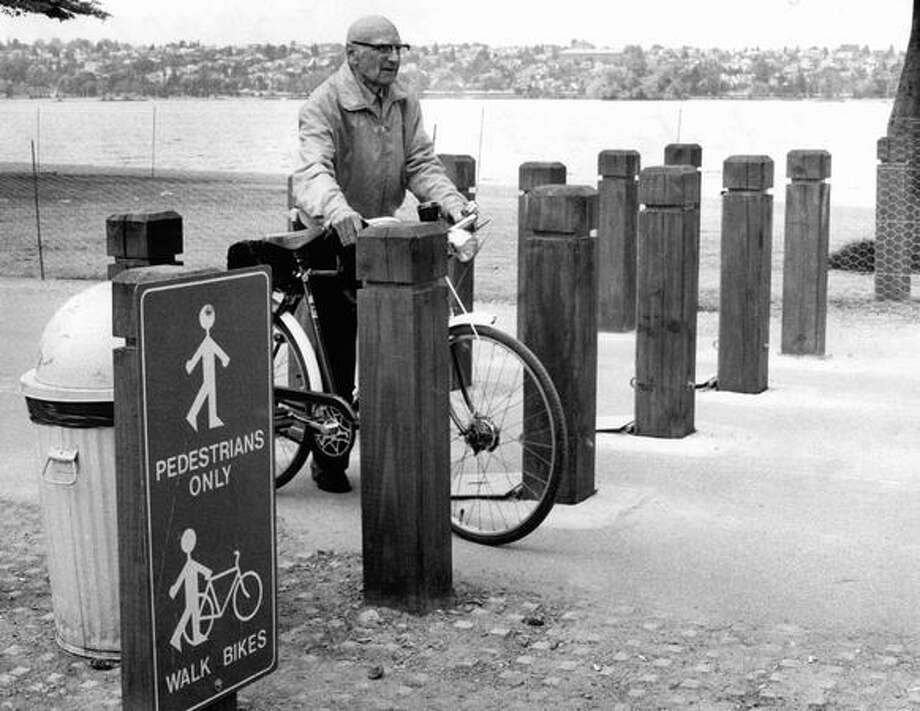 The original caption read: George Lindberg, a young 77, walks his bike through the new obstacles at the Green Lake path designed to stop high-speed bikers. May 6, 1980. Photo: P-I File