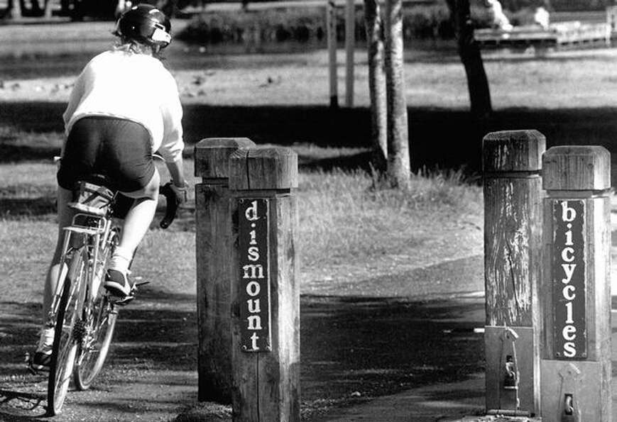 A bike rider ignores signs on the Green Lake path cyclists share with pedestrians, June 17, 1987.