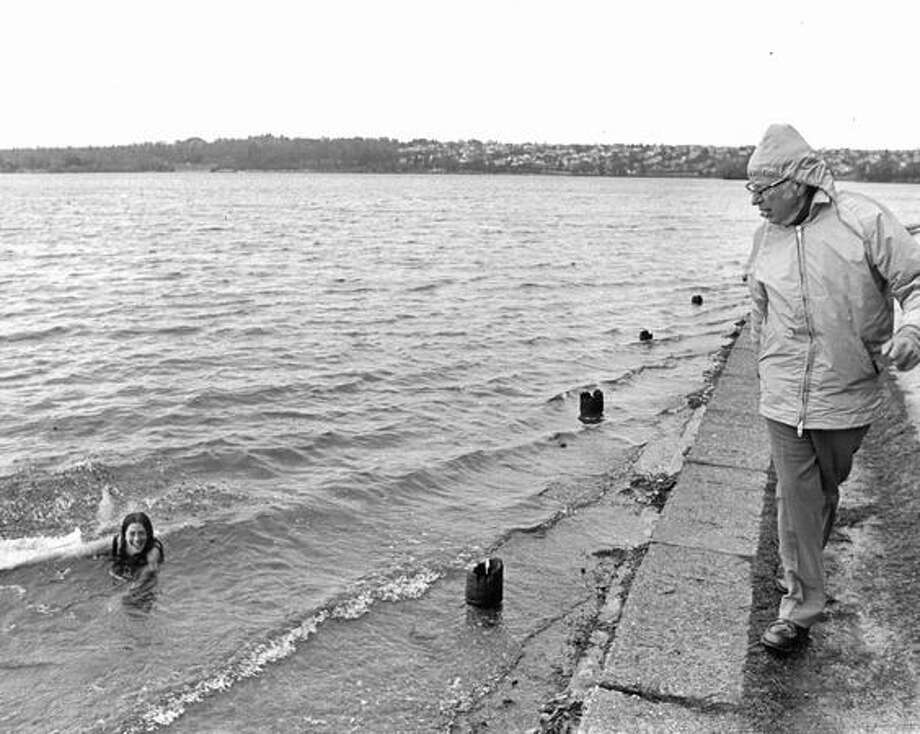 The original caption read: Chester Regan did a double take as he was walking along the shore of Green Lake yesterday in the wind and rain near his home at 7611 W. Green Lake Drive. Out of the chilly watter paddled Sally Jaffee, who is visiting here from Santa Cruz, Calif. Dec. 26, 1976. Photo: P-I File