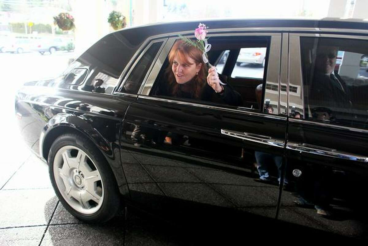 Sarah Ferguson, the Duchess of York, waves to her admirers from a Rolls Royce during a visit to Aegis Living of Shoreline on Tuesday. The Duchess was in town to speak at the Aegis Living Annual Meeting. She also wanted to meet some of the residents of the senior communities.