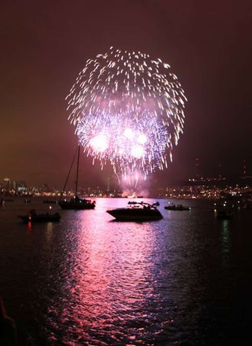 Fireworks explode over Lake Union - and hundreds of boats floating on the lake - during Seattle's Family Fourth celebration.